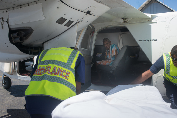 An elderly woman watches as ambulance attendants prepare a stretcher for her following her evaucation from the island of Ambae.