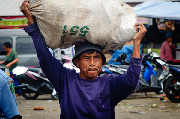 A man carries a heavy load through a rural market in Bali, Indonesia.