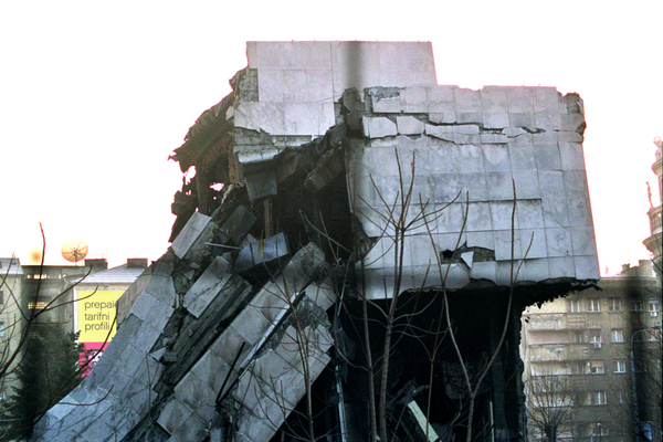 The Yugoslav ministry of Defense building was one of the  first buildings hit during the NATO bombing campaign. This photo was taken through the wire mesh that surrounds it,  hence the cross-hair-like artefact on the image.