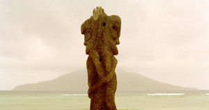 This kind of carving is said to have originated on the  island of Ambrym. This particular example is located outside a hot spring and spa in North Efate island. The island in the background is Emau, part of the Shepherd Islands group.
