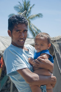 A scene from the camp for Internally Displaced Persons in Dili. Over 40,000 people still occupy camps like this. This young man, named August, took it on himself to give me a tour of the entire camp. He's pictured here with his infant son.