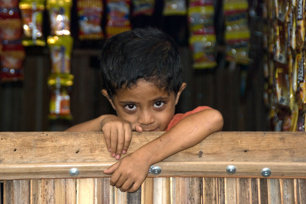This boy's curiousity eventually got the better of him, and he peered over the rail of his mother's roadside stall.