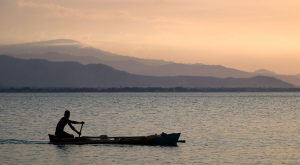 Sunsets in Dili during the dry season are routinely spectacular. Here, a young man ferries water back to his family.