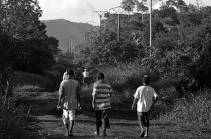 Three youths wander down one of the thoroughfares in Port Vila's Freswota neighbourhood.