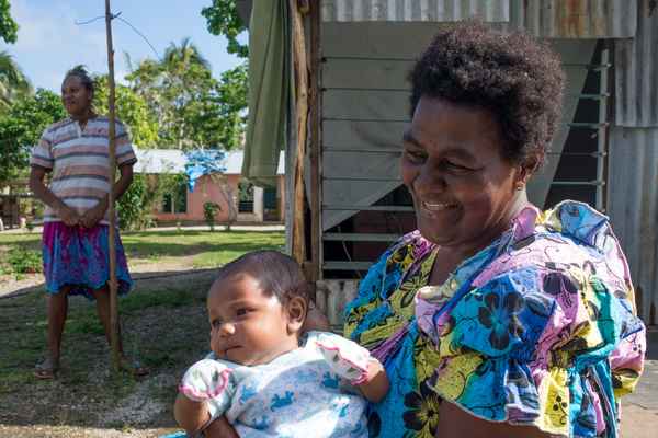 Wilma's grandmother holds Francois, born just a month after cyclone Pam. Wilma stands in the background.