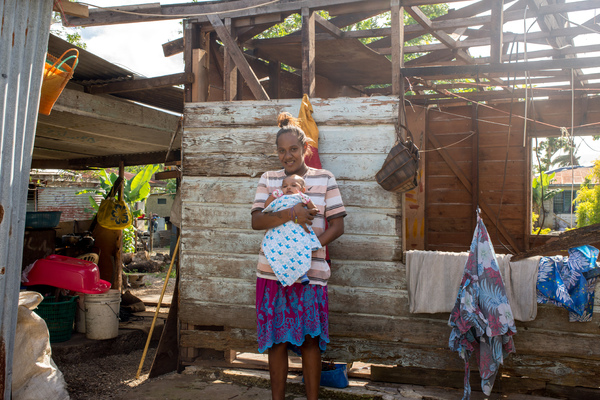 Wilma holds her baby, Francois, in the middle of their family home on Ifira island. It is still in need of major renovations three months after cyclone Pam caused extensive damage.