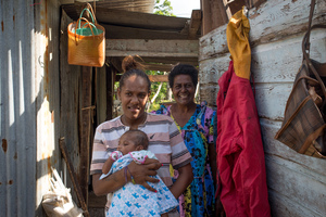 Wilma holds her baby, Francois, in the middle of their family home on Ifira island. It is still in need of major renovations three months after cyclone Pam caused extensive damage. Her mother smiles in the background.