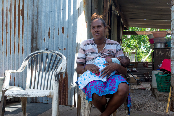 Wilma nurses her baby, Francois, in the middle of their family home on Ifira island. It is still in need of major renovations three months after cyclone Pam caused extensive damage.