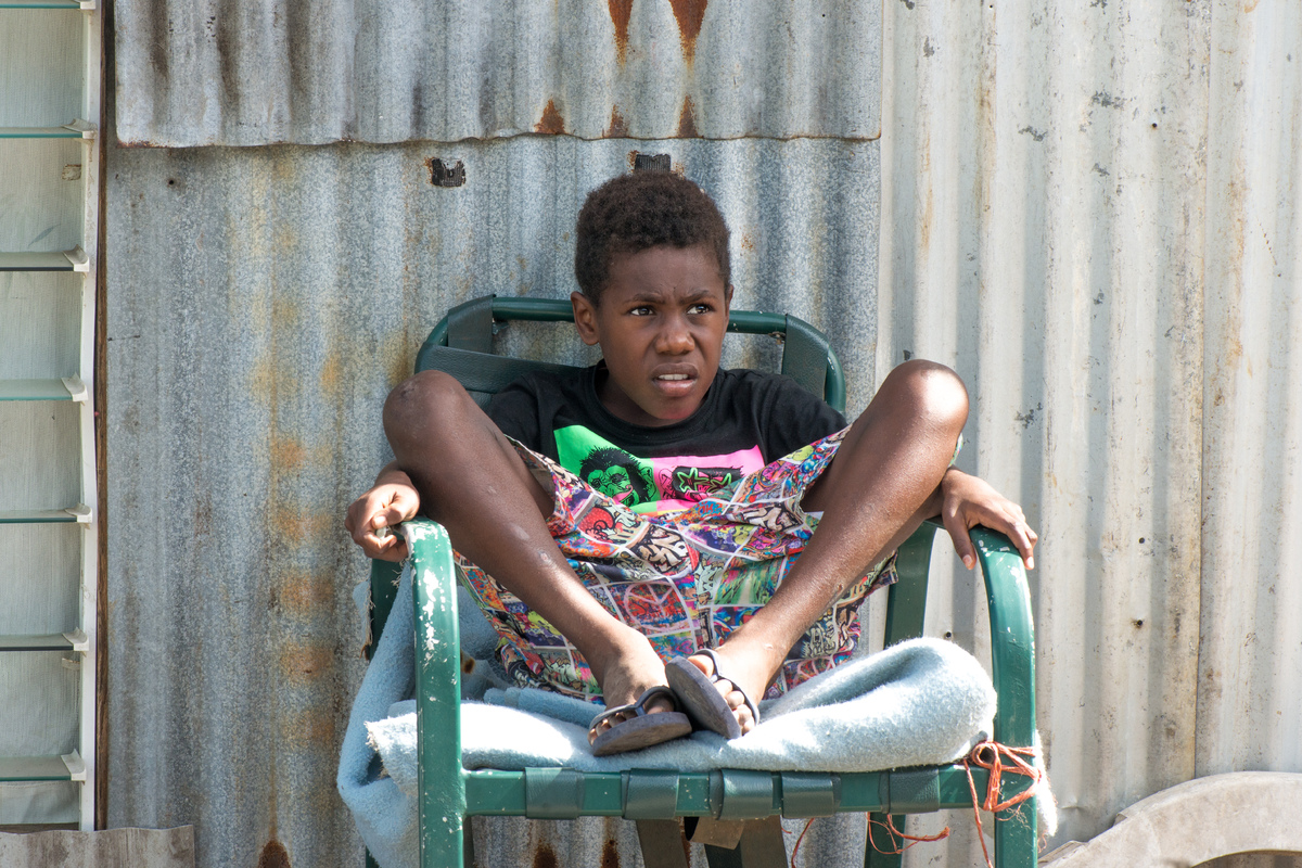 A boy watches as workers repair his home on Ifira island. The house was badly damaged by cyclone Pam.