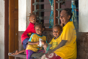 Eva and her children smile as they sit outside the community clinic on Ifira island.