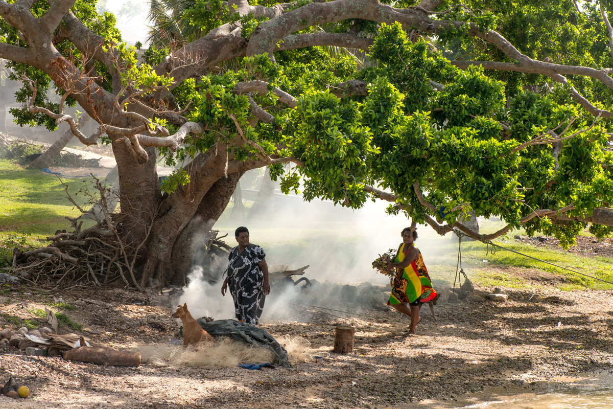 Two women burn off underbrush at the shore of Ifira island. Even three months after cyclone Pam, large piles of windfallen wood and debris still remain.
