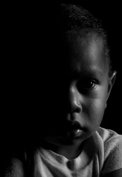 Georgeline's nephew Cyril in the half darkness of his grandfather's house in Lalwari, on Pentecost island.
