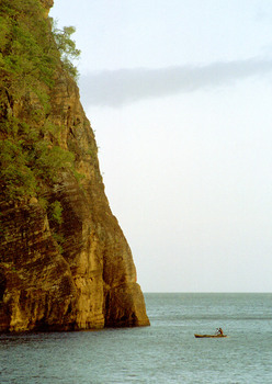 A man paddles his canoe into Lolowei's harbour, sheltered by standing rocks on one side and this massive cliff on the other.