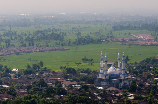 The view from a hilltop temple in Lombok, Indonesia. A mosque dominates the landscape of simple village houses and rice paddies.