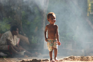 A child emerges from the smoke of the cookfire and runs to greet his father.