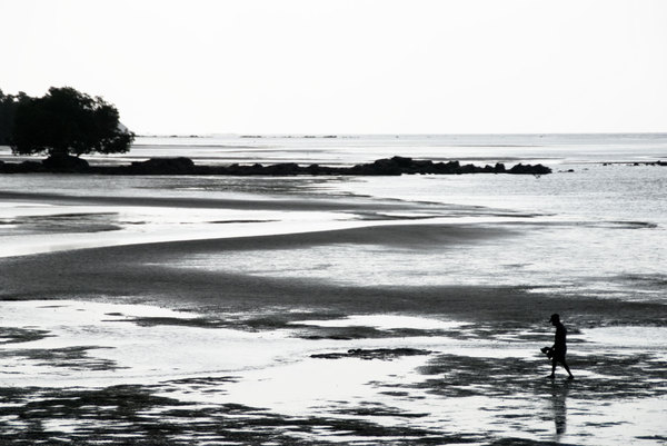 A man hunts for shell fish at low tide.