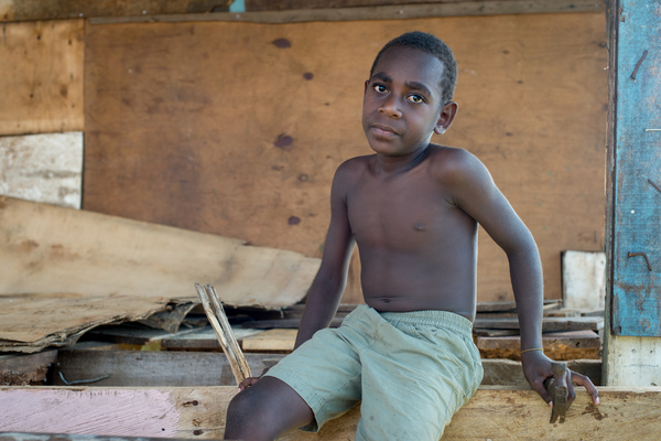 A boy with a hammer sits in a half-finished house.