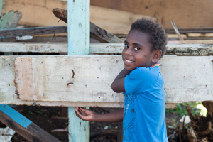 A girl stands beside a half-constructed house made from salvaged materials.