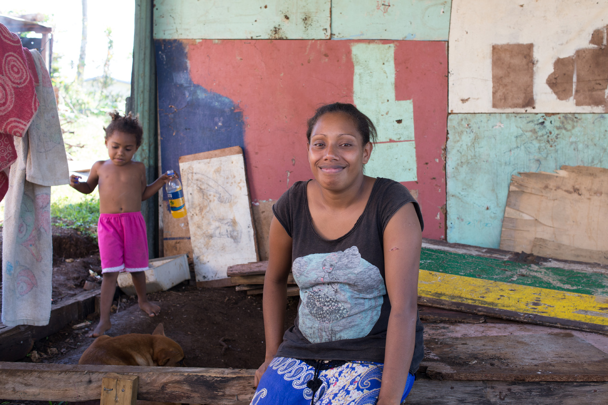 Rachel's mother Melissa sits in a half-finished house built from salvaged materials.