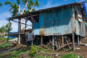 Rachel's father stands in front of the makeshift house they built for the land-owner out of salvaged parts.