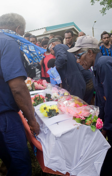Grave workers struggle with the coffin as family members crowd around.