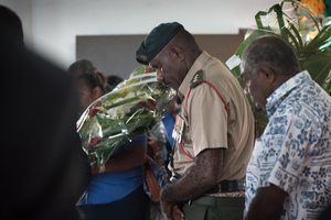 An officer of the Vanuatu Mobile Force bows his head as he pays his respects to  President Baldwin Lonsdale, whose body lies in state.