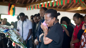 A woman weeps as she accompanies the Prime Minister (background) to pay their respects to President Baldwin Lonsdale, whose body lies in state at the State House Nakamal.