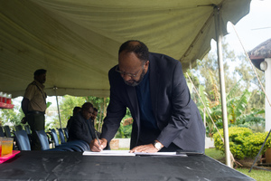 Prime Minister Charlot Salwai signs the condolence book as President Baldwin Lonsdale lies in state.