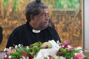 A clergyman, red-eyed, waits to pay his respects to Edward Natapei, whose body lies in state at Parliament.