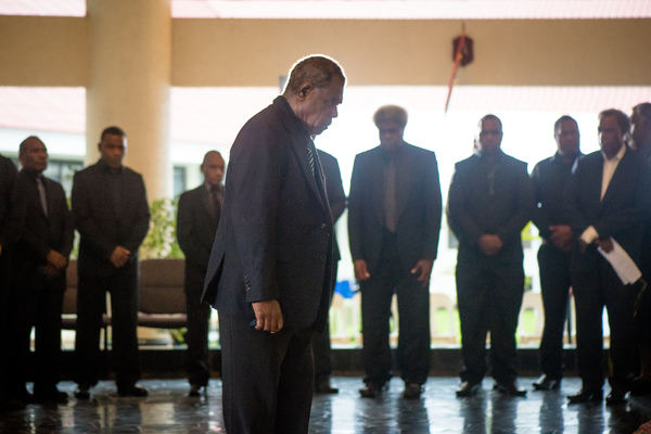 Speaker and Acting Head of State Esmon Saimon bows before the body of President Baldwin Lonsdale.