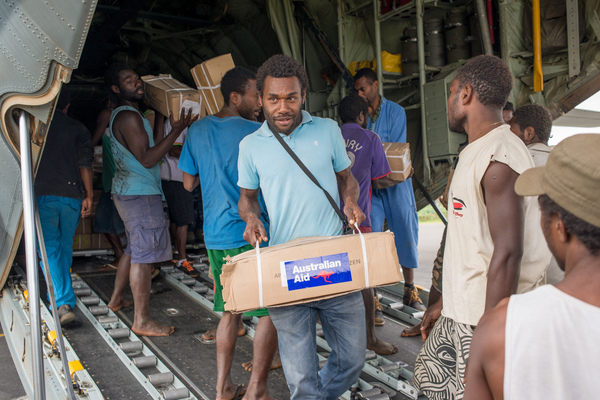 Australian governor general Peter Cosgrove's visit to Tanna underlines how much work remains to be done in the aftermath of cyclone Pam. Tannese men offload bush knives and other essentials from an RAAF relief flight.