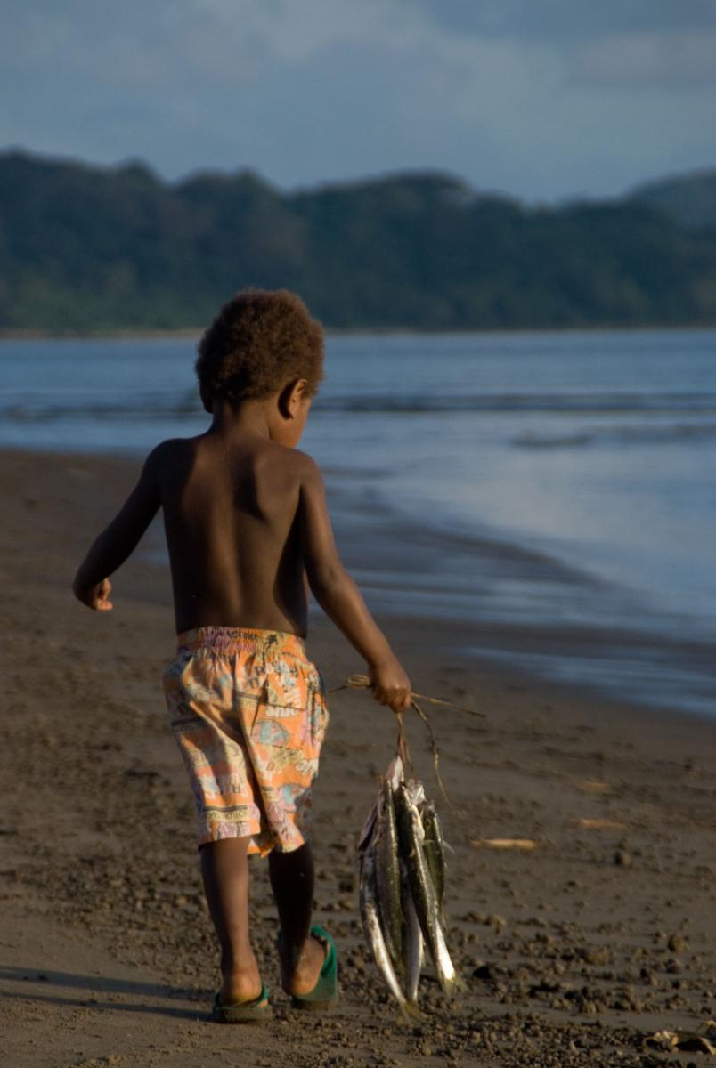 A young boy carries the day's catch home along Blacksand beach.