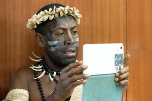 Old meets new: A Futunese Kastom Dancer records a speech by prime minister Charlot Salwai on on tablet during the opening ceremony of ICT Days in Port Vila.