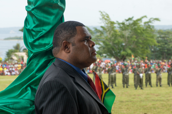 A protocol officer stands to attention as the national anthem is played.