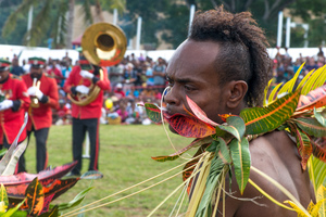 A kastom dancer from Mere Lava performs while the VMF band plays in the background.