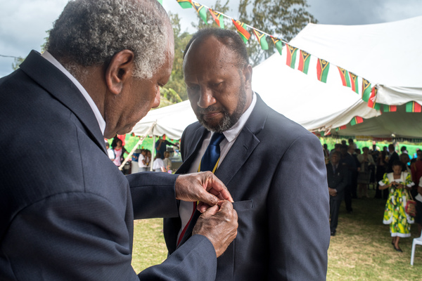 Prime Minister Charlot Salwai receives a distinguished service medal from President Baldwin Lonsdale.