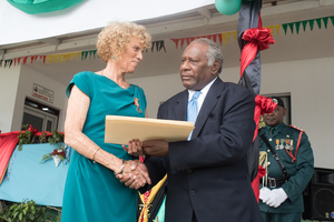 The principal of the Port Vila Internatonal School receives receives a meritorious service medal from President Baldwin Lonsdale.