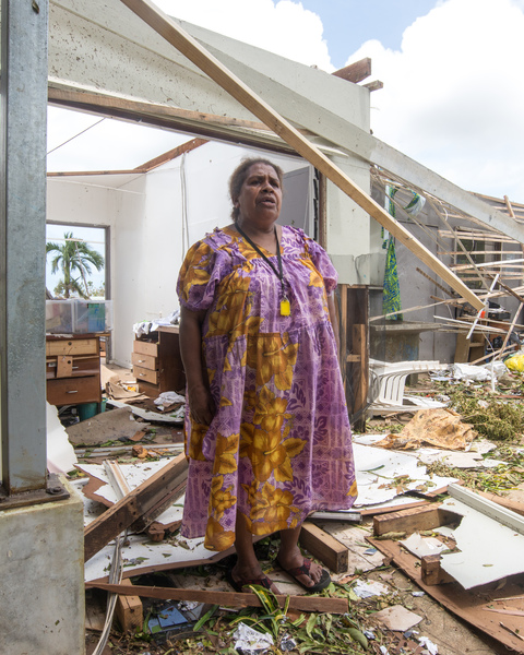 A young woman smiles in wreckage the day after cyclone Pam destroyed her mother's handicrafts stall at Port Vila's seafront. In the background is a sign exhorting people to keep Port Vila clean.