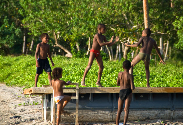 A group of young boys position themselves to defend their possession of walking-about rights on a beached pontoon.