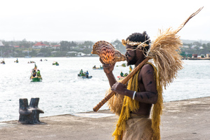 A Futunese warrior blows a conch shell trumpet to welcome a flotilla of small craft during the ground-breaking ceremony for the Lapetasi wharf project.
