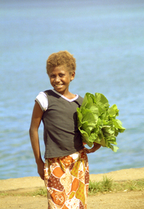 A young girl carrying local lettuce waits for the  next boat to nearby Ifira island.