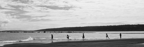 A line of children speeds into the surf.