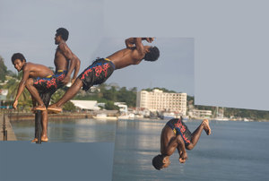 A young man does a backflip off the sea wall ladder.