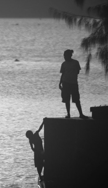 Two children playing down the near old Rossi wharf on Port Vila's Seafront area.