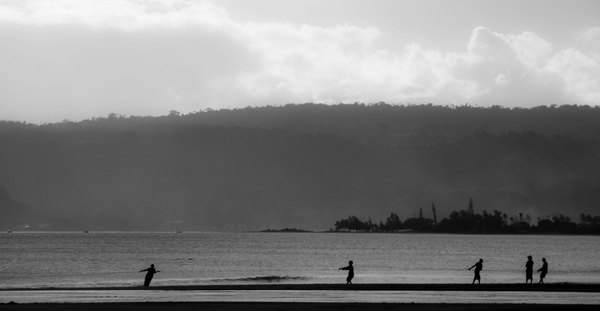 Silhouetted against the afternoon sun, people from Blacksand pull in their fishing net.