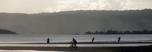 Silhouetted against the afternoon sun, three people pull in their fishing net.