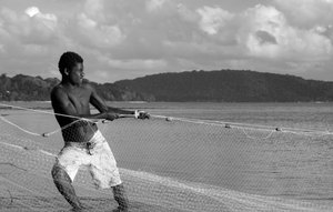 A young Tannese man strains against the weight of the net.