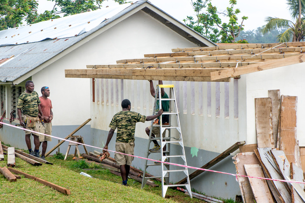 Members of the Engineering company of the Vanuatu Mobile Force rebuild a classroom that had been badly damaged by cyclone Pam. Without the assistance of UNICEF and other agencies, the school would have been forced to close, leaving the education of hundreds of students in doubt.