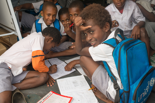 Students from Vila North school in Port Vila work inside the tent that has been their classroom since cyclone Pam destroyed part of the school. UNICEF's extensive support has made it possible for Vila North to continue providing an education for hundreds of children.
