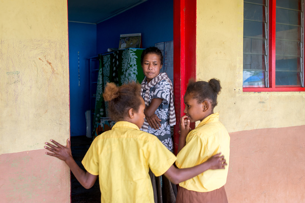 Children from St Joseph school near Port Vila enter the classroom as their teacher looks on.